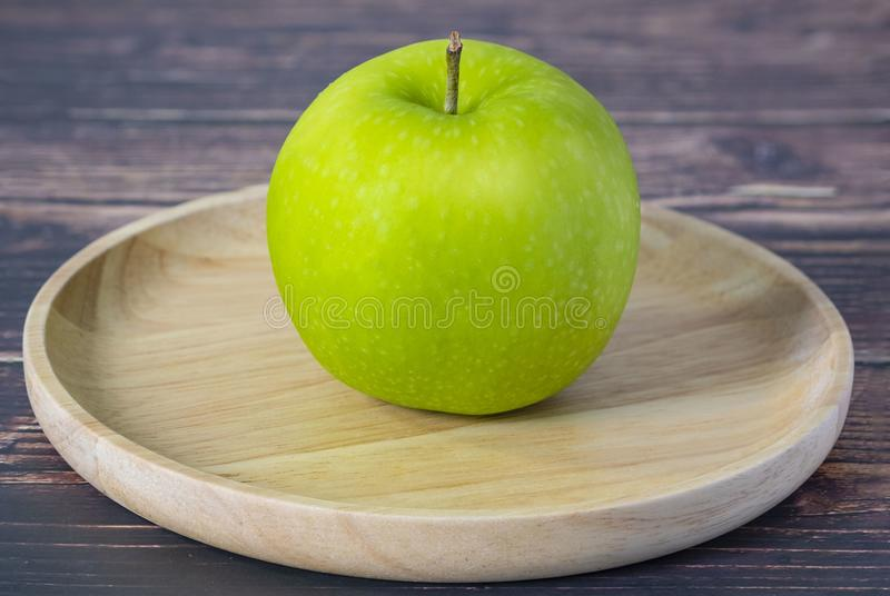 Fresh green apple in dish wooden, on old wood table royalty free stock image