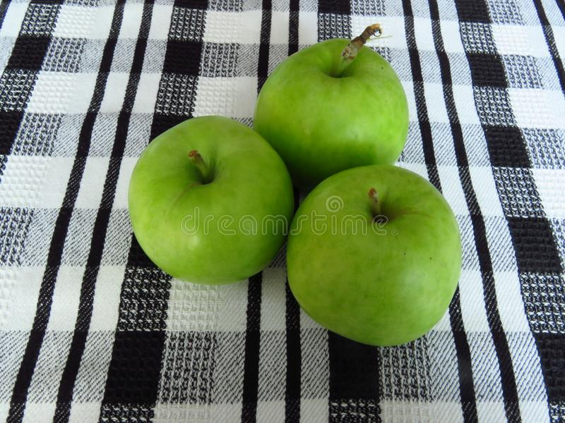 Fresh green apples on black and white tablecloth. Healthy, organic fruit. Orchard production, harvest, crop, diet, healthy food concept royalty free stock photography
