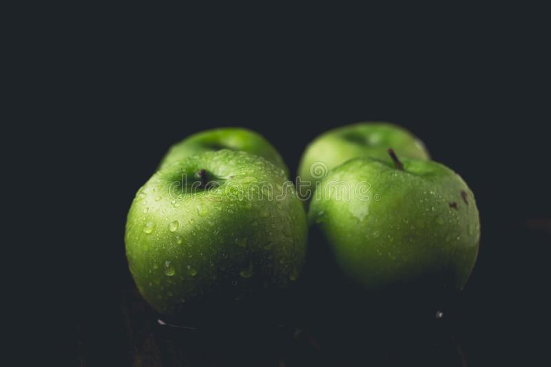 Fresh green apples in low light areas and black background. S stock photos