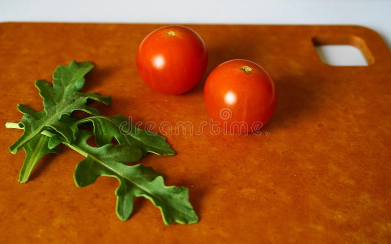 Fresh green arugula leaves and cherry tomatoes on hardboard. royalty free stock photography