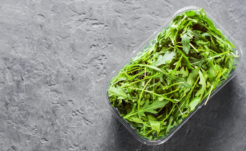 Fresh green arugula leaves in a plastic package box on Dark grey black slate background with copy space royalty free stock images
