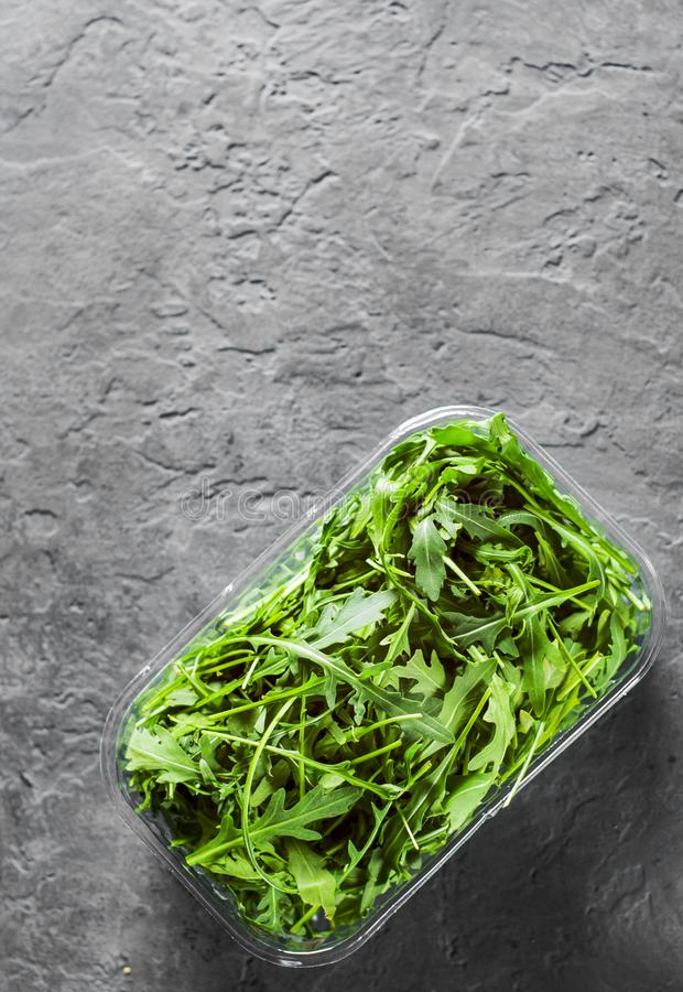 Fresh green arugula leaves in a plastic package box on Dark grey black slate background with copy space stock images