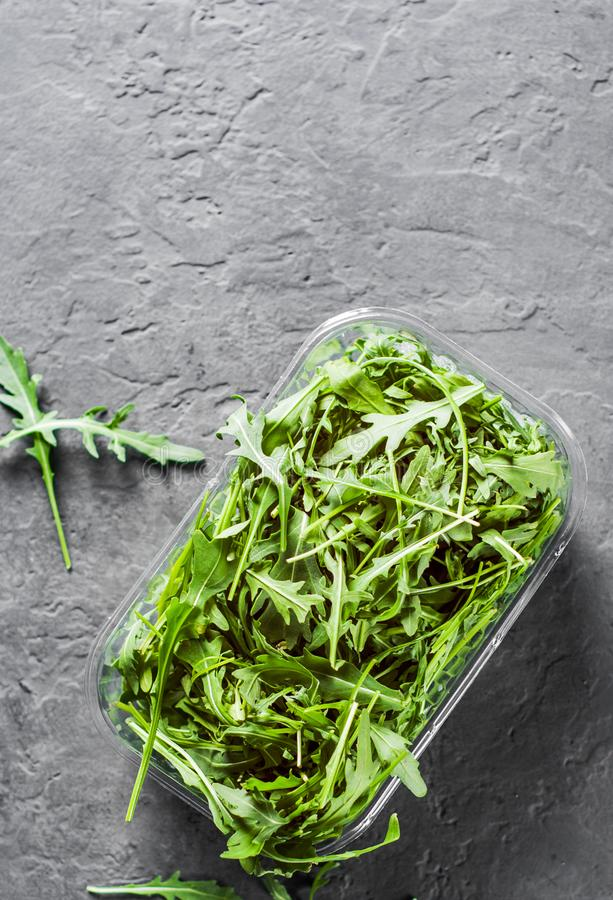 Fresh green arugula leaves in a plastic package box on Dark grey black slate background with copy space royalty free stock photos