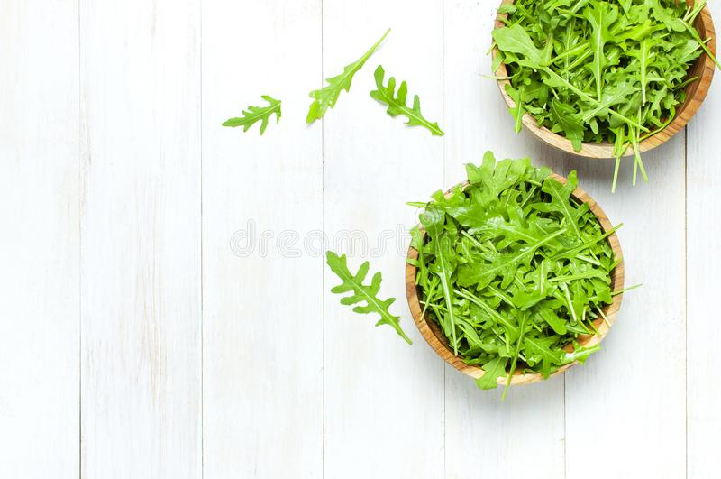Fresh green arugula leaves on wooden bowl, rucola salad on white wooden rustic background top view with place for text. Rocket. Salad or arugula, healthy food royalty free stock images