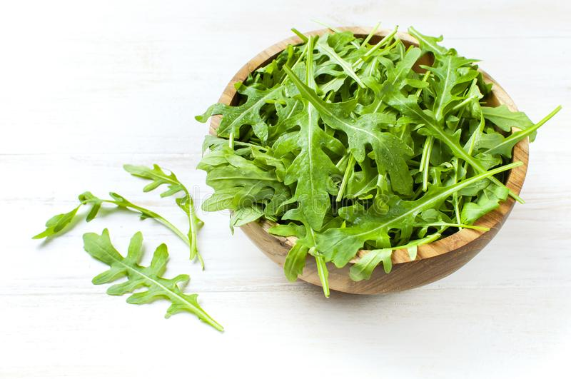 Fresh green arugula leaves on wooden bowl, rucola salad on white wooden rustic background with place for text. Selective focus. Rocket salad or arugula royalty free stock images