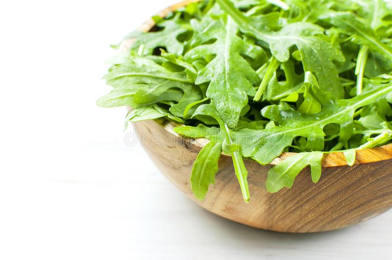 Fresh green arugula leaves on wooden bowl, rucola salad on white wooden rustic background with place for text. Selective focus. Rocket salad or arugula royalty free stock image