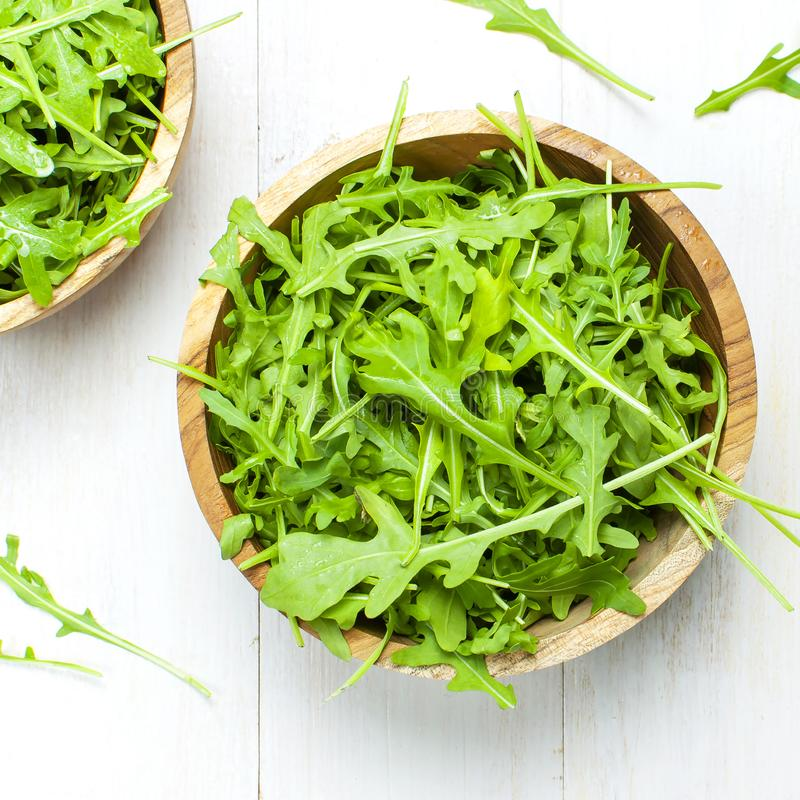 Fresh green arugula leaves on wooden bowl, rucola salad on white wooden rustic background top view with place for text. Rocket. Salad or arugula, healthy food stock photo