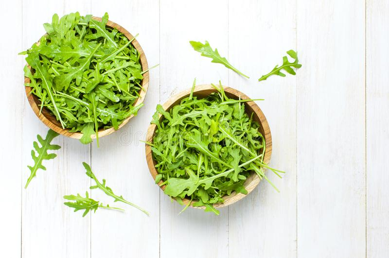 Fresh green arugula leaves on wooden bowl, rucola salad on white wooden rustic background top view with place for text. Rocket. Salad or arugula, healthy food stock photos