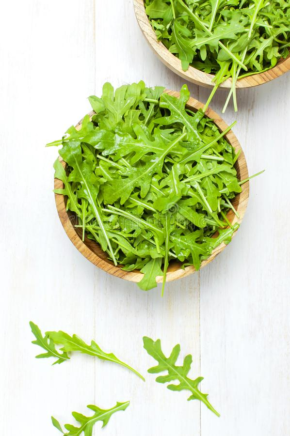 Fresh green arugula leaves on wooden bowl, rucola salad on white wooden rustic background top view with place for text. Rocket. Salad or arugula, healthy food stock image