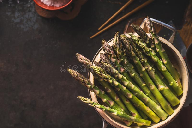 Fresh green asparagus in asian bamboo steamer on dark background, top view. Copy space. Healthy eating and cooking concept. Diet. Food royalty free stock photo