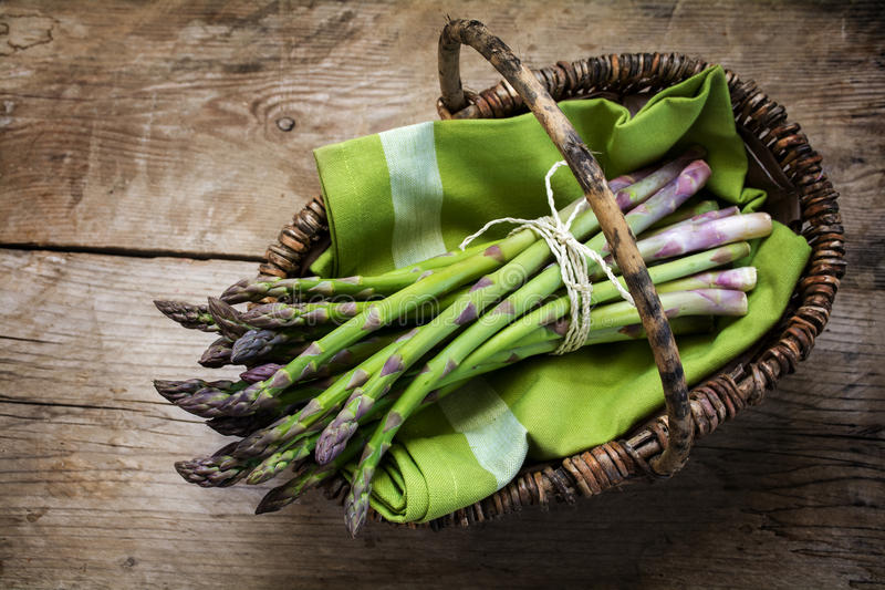 Fresh green asparagus in a basket on a rustic wooden table, view royalty free stock photo