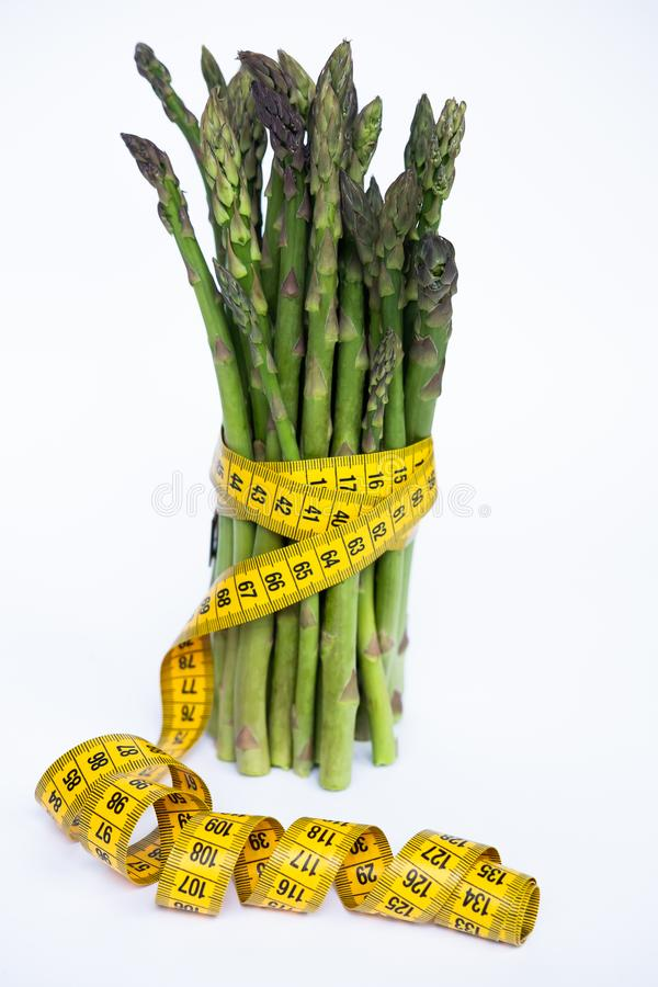 Fresh green asparagus bunch with measuring tape isolated over white background. stock images