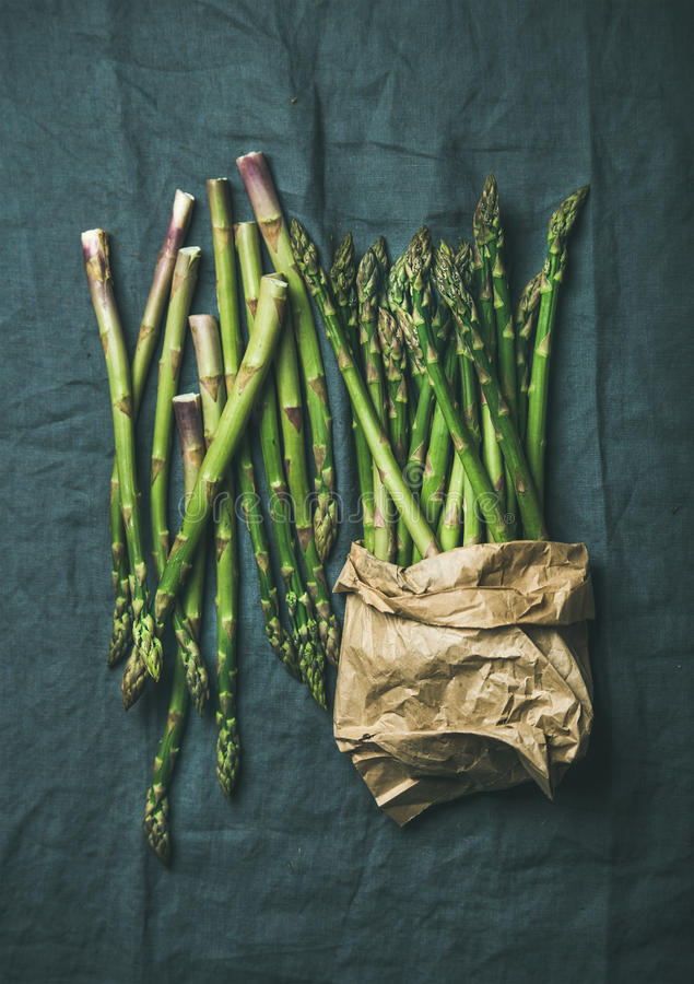 Fresh green asparagus in craft paper bag over grey cloth. Fresh green asparagus in craft paper bag over dark grey linen table cloth background, top view royalty free stock photography