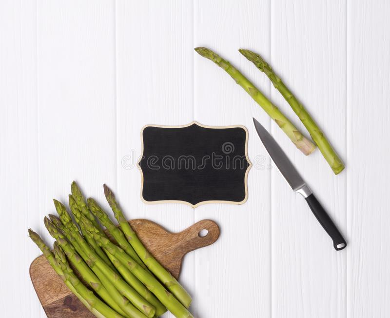 Fresh green asparagus on cutting board with knife at white wooden table background stock images