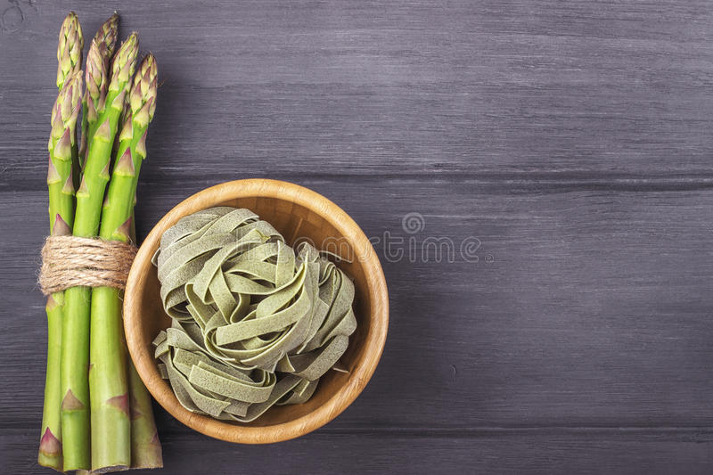 Fresh green asparagus and fettuccine italian pasta in bowl on wooden rustic background stock image