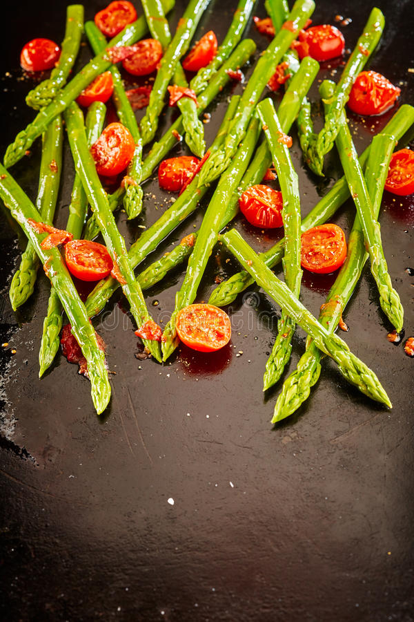 Fresh green asparagus spears with roasted tomatoes royalty free stock photography