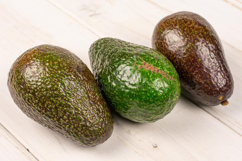 Fresh green avocado on grey wood stock images