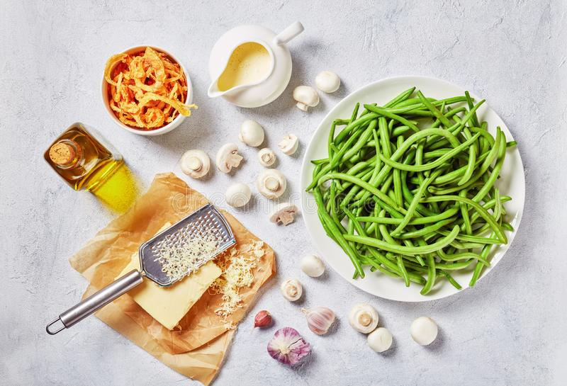 Fresh green beans, cheese, fried onion, cream. Fresh green bean in pods on a white plate on a concrete table with crispy french fried onion rings cheese royalty free stock photography