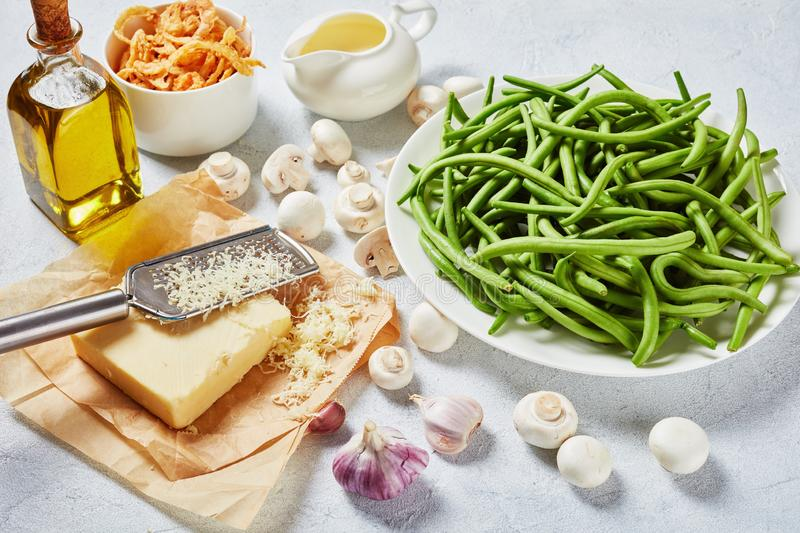 Fresh green beans, cheese, fried onions, cream. Fresh green bean in pods on a white plate on a concrete table with crispy french fried onion rings cheese stock photo