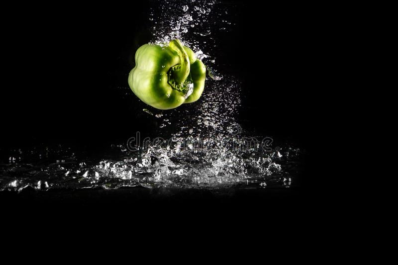 Fresh Green Bell Pepper with Water Splash and Bubble Isolated. Pepper Copy Space. Juicy Green Paprika Dropped Falling into Water. On Black Background royalty free stock photos