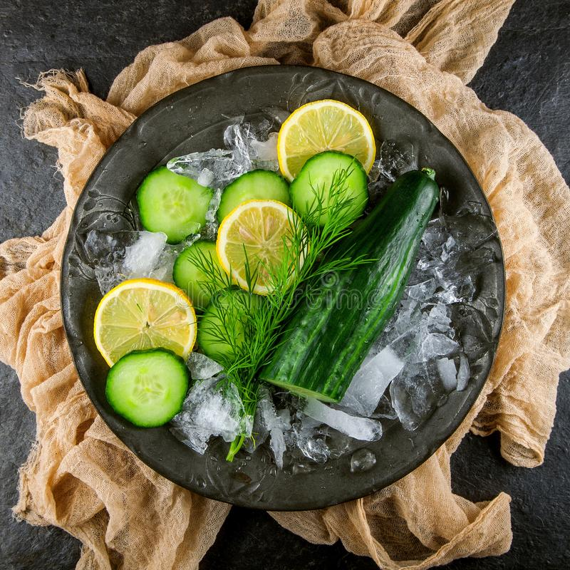Fresh green cucumber with ice and lemon stock images