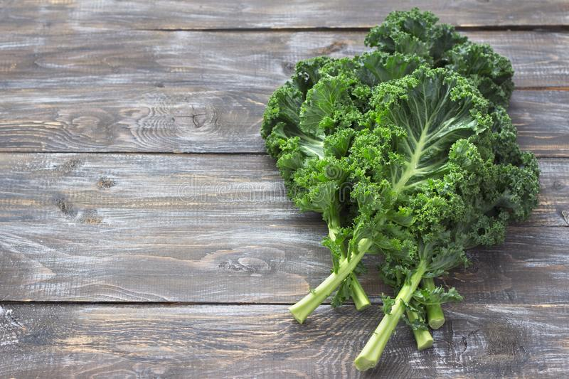 Fresh green curly kale leaves on a cutting board on a wooden table stock images