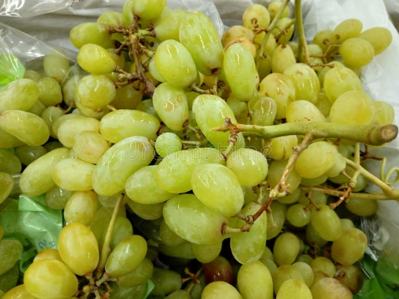 Fresh green grapes for sale at a market stock image