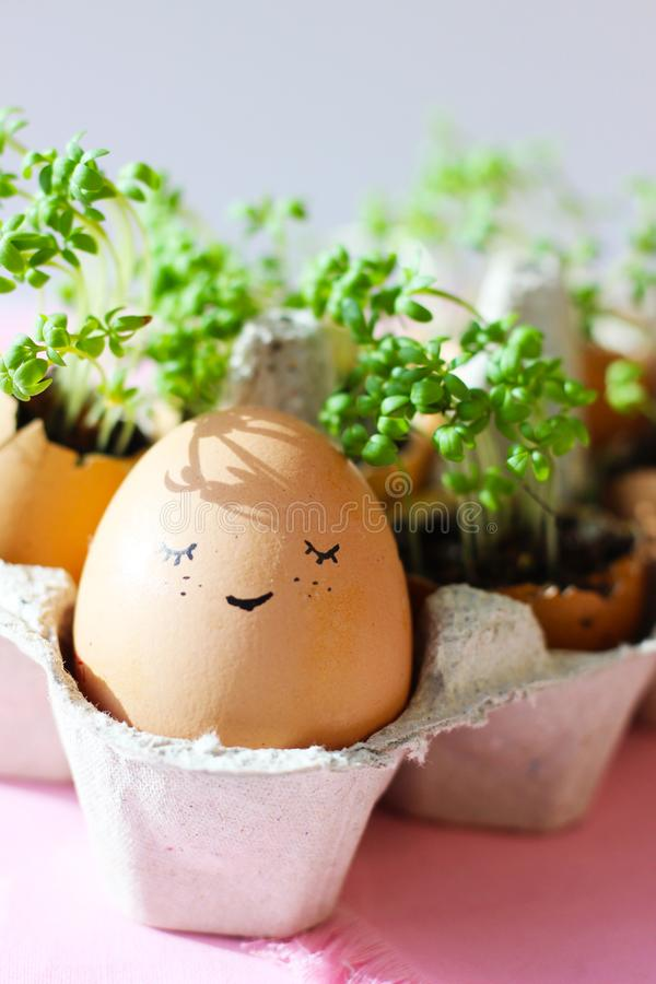The fresh green grass growing in an egg shell with the funny persons drawn on it. The idea of spring creativity for stock photo