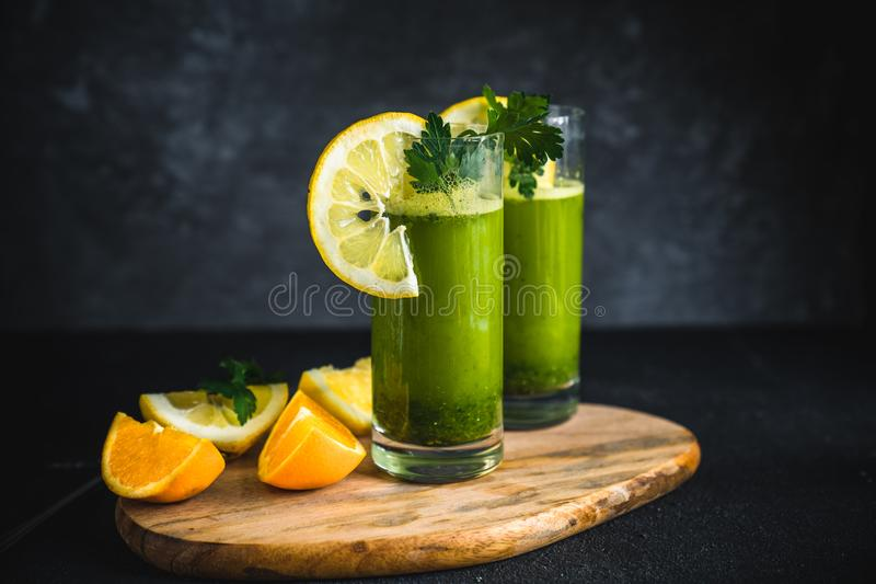 Fresh green juice made from parsley, oranges and lemons. Green smoothie with parsley on black background stock photo