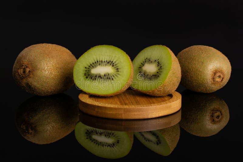 Fresh green kiwi isolated on black glass royalty free stock photos