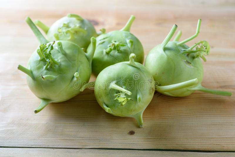 Fresh green kohlrabi or german turnip or turnip cabbage on wood background. stock photography