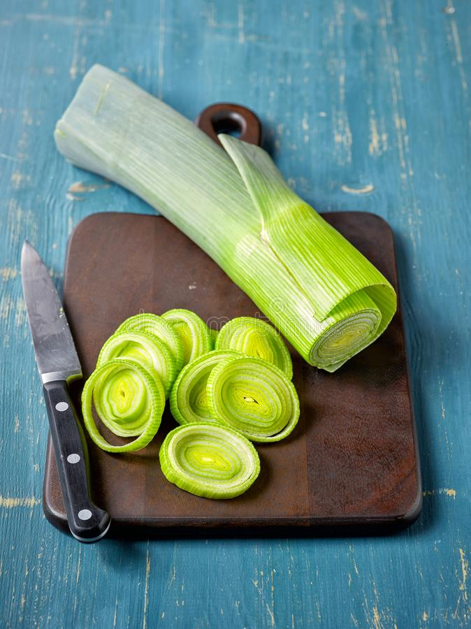 Fresh green leek on wooden cutting board stock image