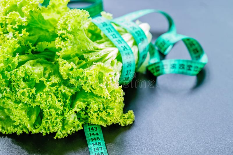Fresh green lettuce salad leaves with measuring tape on dark background. The concept of a healthy lifestyle, diet, healthy food. stock photos