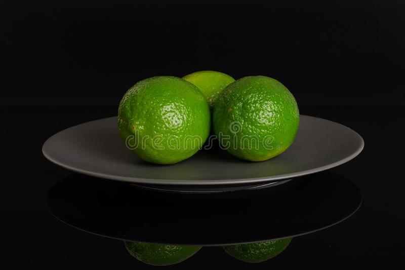Fresh green lime isolated on black glass royalty free stock photography