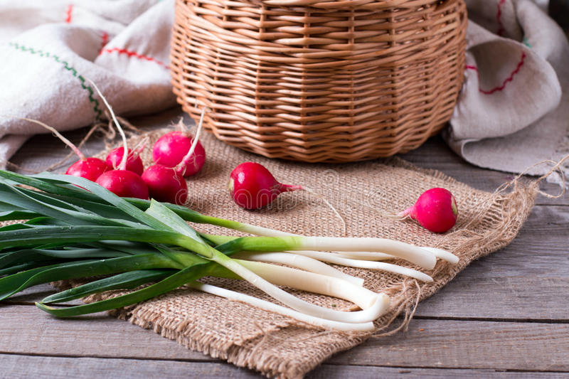 Fresh green onion and radishes on old wooden table stock photos