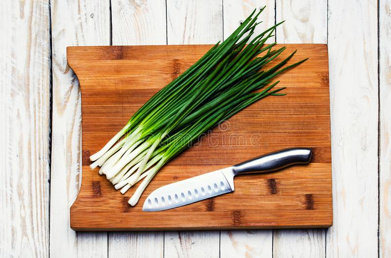 Fresh green onions on a cutting board royalty free stock images