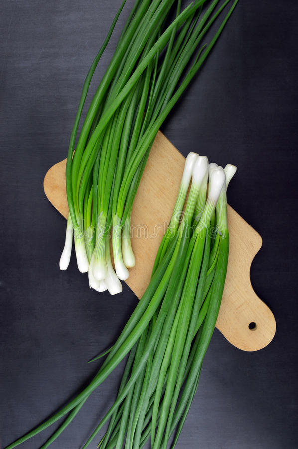 Fresh green onions on a cutting board.Top view. A bunch of fresh chives on a wooden cutting board. Spring. Vitamins. Cooking. Fresh organic produce. Green stock photos