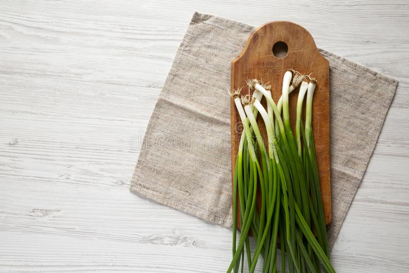 Fresh green onions on a cutting board on a white wooden table, top view. From above, overhead, flat lay. Copy space.  stock image