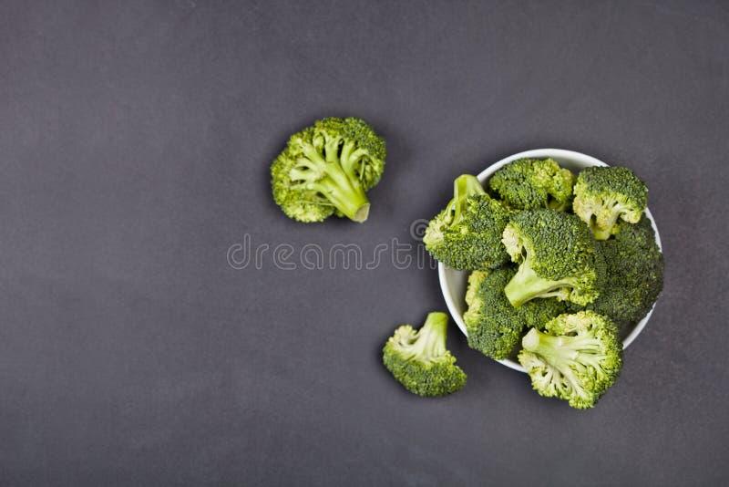 Fresh green organic broccoli in white bowl on black board background stock photo