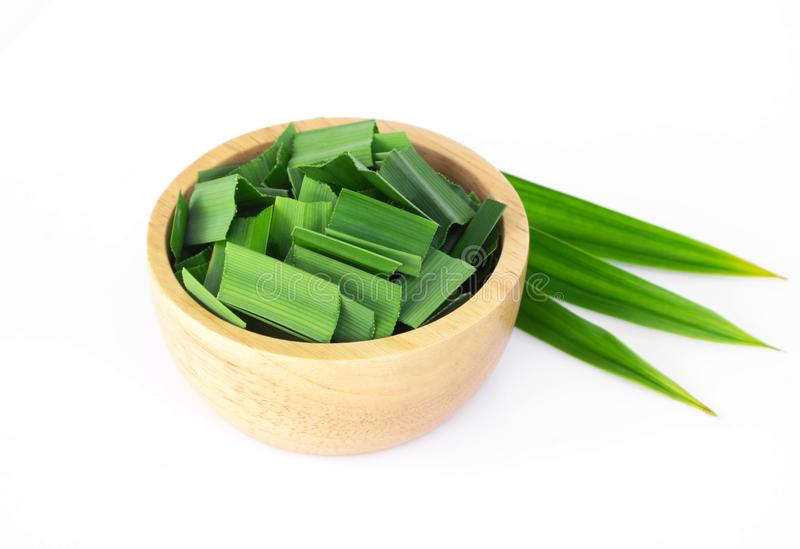 Fresh green pandan leaves with slice in wood bowl isolated on white background. Fresh green pandan leaves with slice in wood bowl isolated stock image