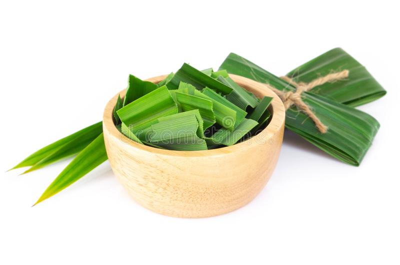 Fresh green pandan leaves with slice in wood bowl isolated on white background. Fresh green pandan leaves with slice in wood bowl isolated stock photos