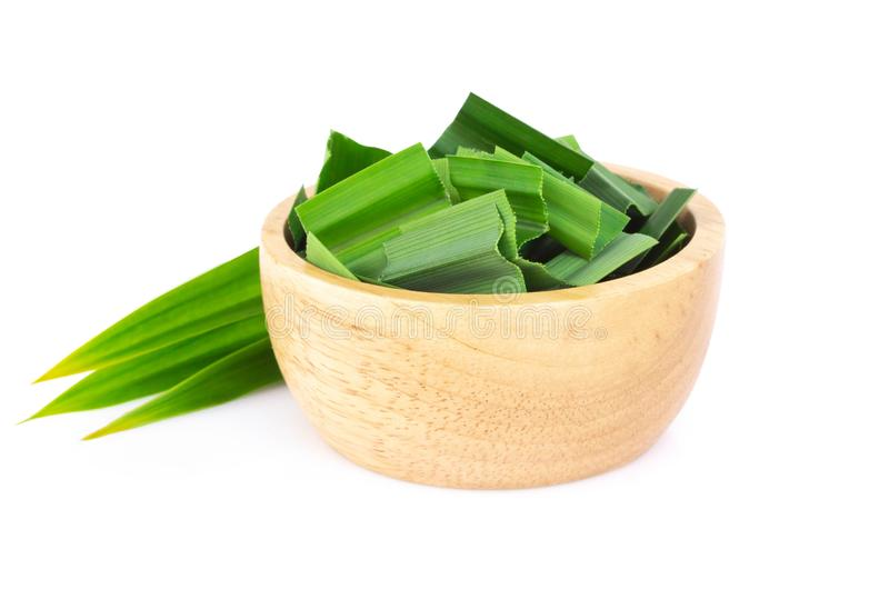 Fresh green pandan leaves with slice in wood bowl isolated on white background. Fresh green pandan leaves with slice in wood bowl isolated on white stock photography
