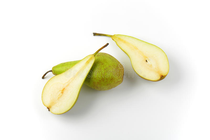 Fresh green pears. One whole pear and two pear halves royalty free stock photos