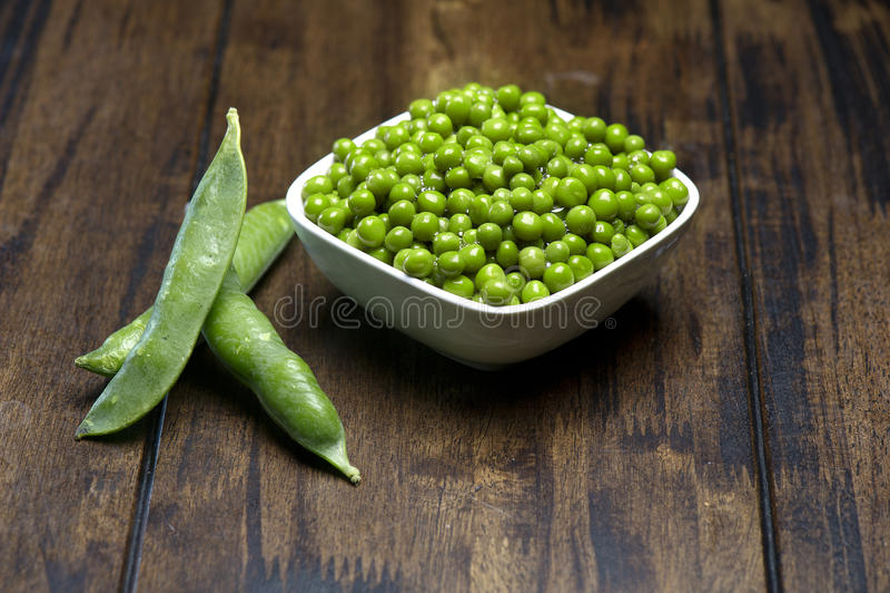 Fresh green peas in a white pot stock photo