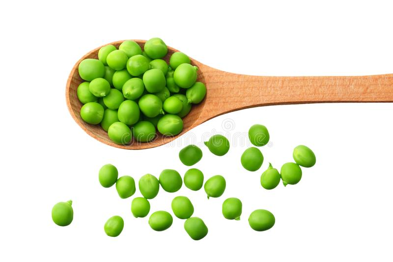 Fresh green peas in a wooden spoon isolated on a white background. top view stock image