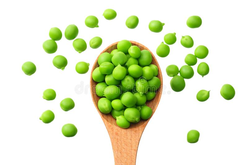 Fresh green peas in a wooden spoon isolated on a white background. top view royalty free stock photo