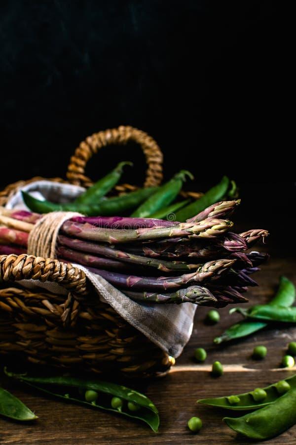 Fresh green and purple asparagus, green peas in wicker basket, hard light, deep shadows, dark background - gourmet organic food stock image