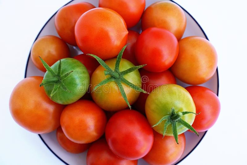 Fresh green and red cherry tomatoes on a white saucer, top view stock image
