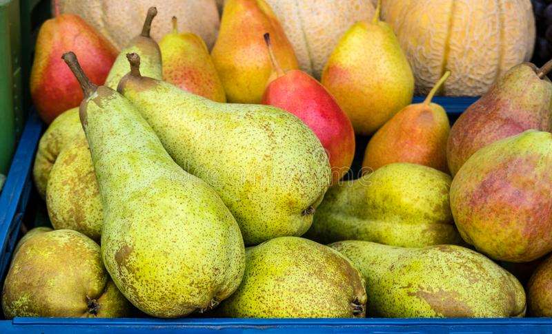 Fresh Green and Red Pears in a basket, on sale on market stock photography