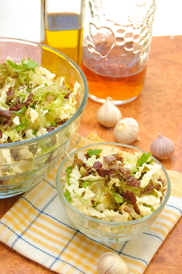Fresh green salad. In a transparent bowl on the kitchen table royalty free stock photo
